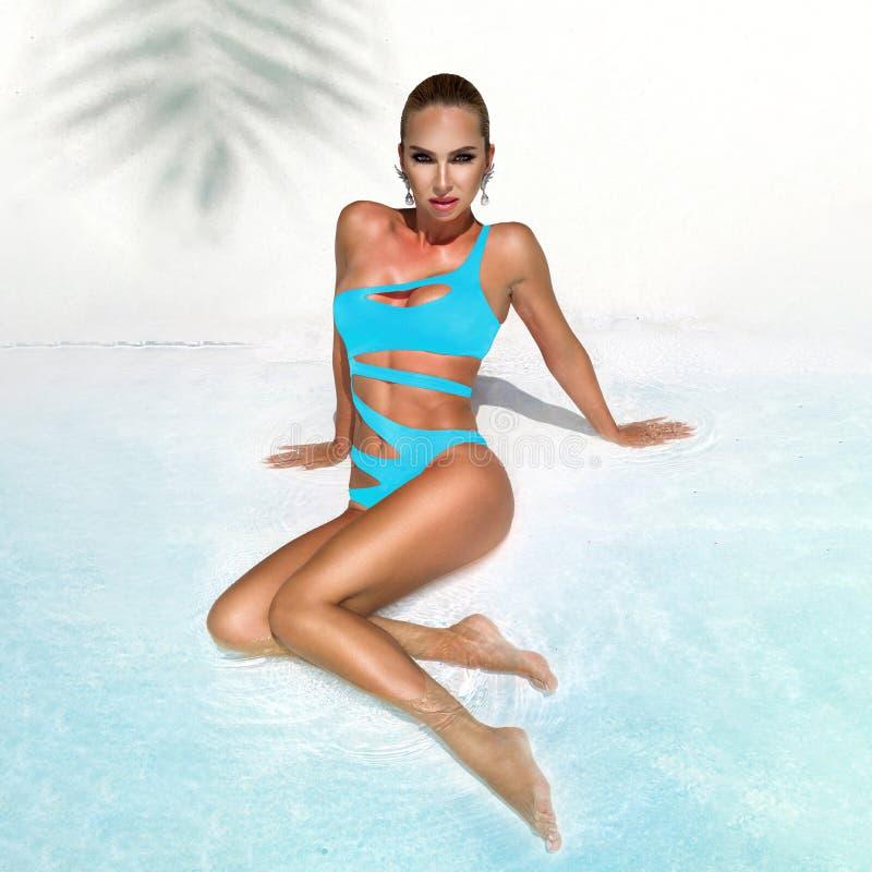 Η κομψή προκλητική γυναίκα στο μπλε μπικίνι στο ήλιος-μαυρισμένο λεπτό και εύμορφο σώμα θέτει κοντά στην πισίνα - εικόνα στοκ φωτογραφία με δικαίωμα ελεύθερης χρήσης
