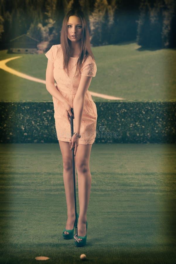 Η κομψή όμορφη γυναίκα παίζει το γκολφ στοκ φωτογραφίες με δικαίωμα ελεύθερης χρήσης