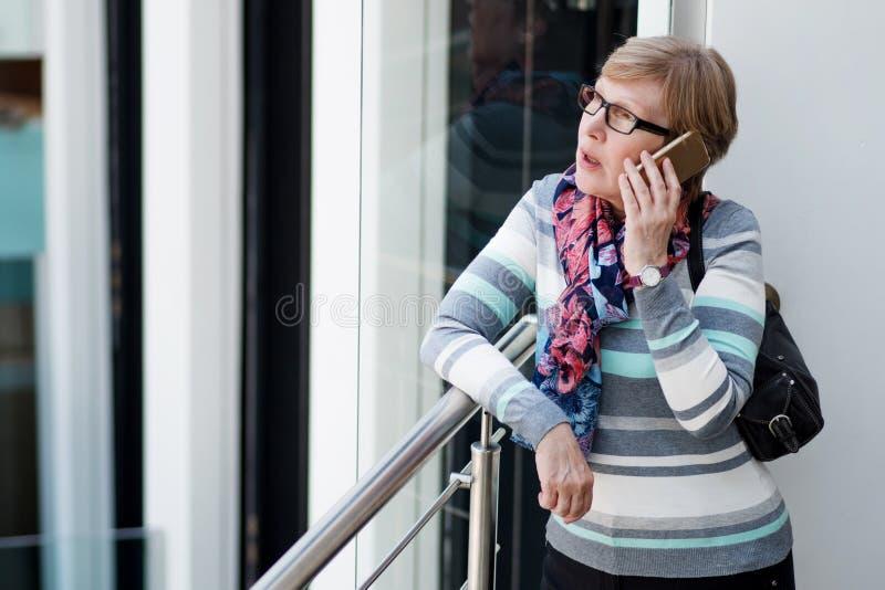 Η κομψή ώριμη γυναίκα χρησιμοποιεί το smartphone, τηλεφωνική συζήτηση, πορτρέτο στη λεωφόρο στοκ φωτογραφία με δικαίωμα ελεύθερης χρήσης