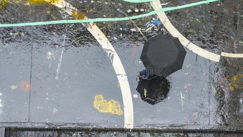 Η κορυφή της μαύρων ομπρέλας και του προσώπου περπατά στο υγρό μαύρο πάτωμα με το ρ στοκ φωτογραφία με δικαίωμα ελεύθερης χρήσης