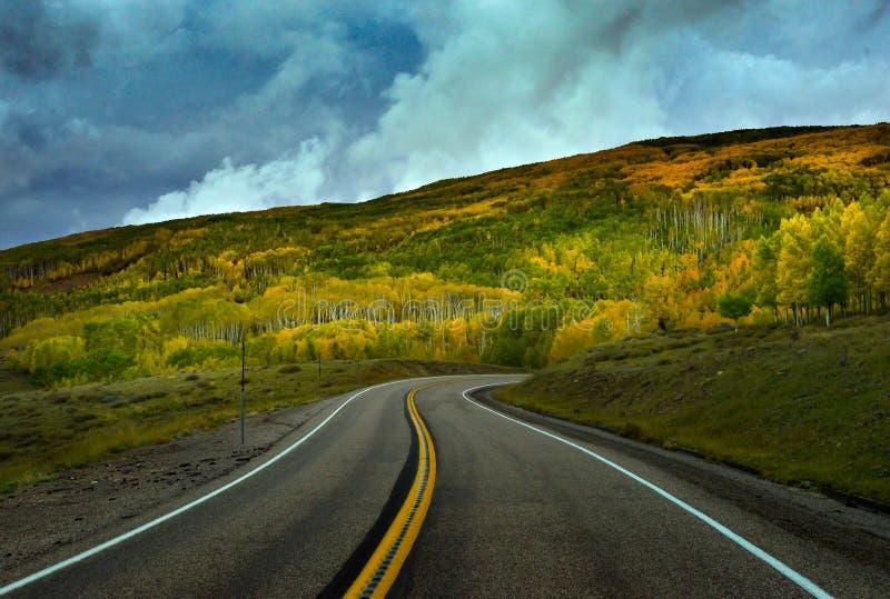 Η κορυφογραμμή του φθινοπώρου πέρα από τον κυρτό δρόμο κάτω από το συννεφιάζω ουρανό στοκ εικόνες
