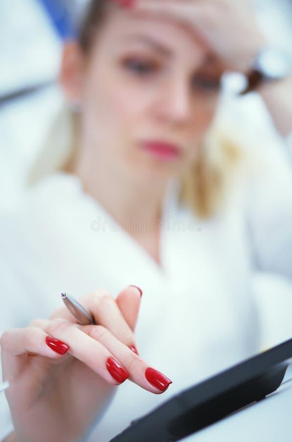 Η κουρασμένη επιχειρησιακή γυναίκα ή ο θηλυκός λογιστής υπολογίζει τις απώλειες σε έναν υπολογιστή στην αρχή Φωτογραφία με το βάθ στοκ εικόνα με δικαίωμα ελεύθερης χρήσης