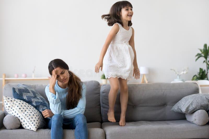 Η κουρασμένη μητέρα έχει τον πονοκέφαλο λίγη κόρη που πηδά στον καναπέ στοκ φωτογραφίες με δικαίωμα ελεύθερης χρήσης
