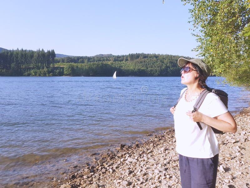 Η κουρασμένη ταξιδιωτική γυναίκα με ένα σακίδιο πλάτης περπατά από το δάσος στοκ εικόνες