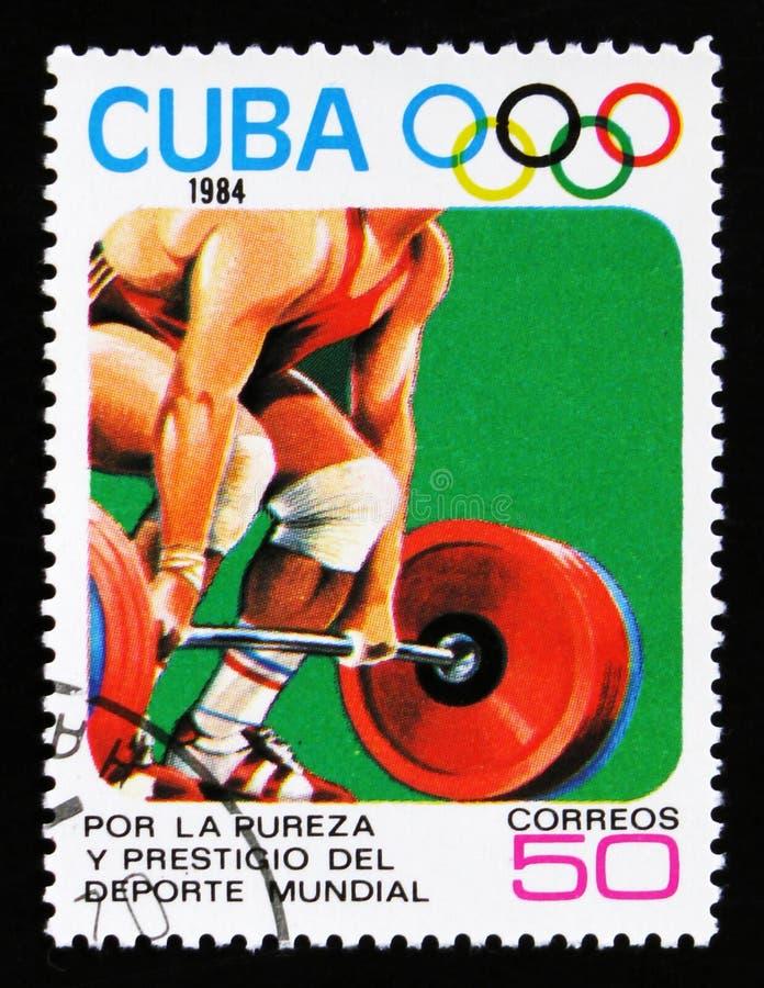 Η Κούβα παρουσιάζει ανυψωτή βάρους, 23οι θερινοί Ολυμπιακοί Αγώνες, Los Anbgeles το 1984, ΗΠΑ, circa το 1984 στοκ εικόνα
