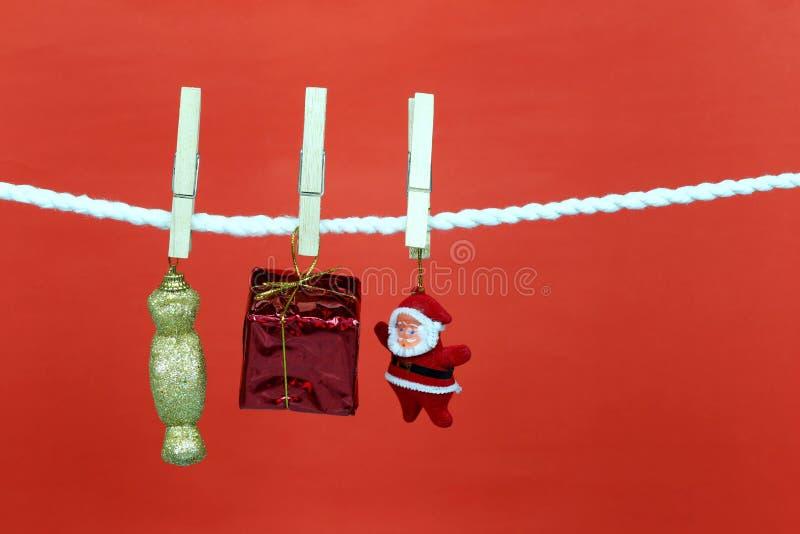 Η κούκλα Santa κρεμά στη σκοινί για άπλωμα και έχει το διάστημα αντιγράφων με το κόκκινο υπόβαθρο στοκ εικόνες