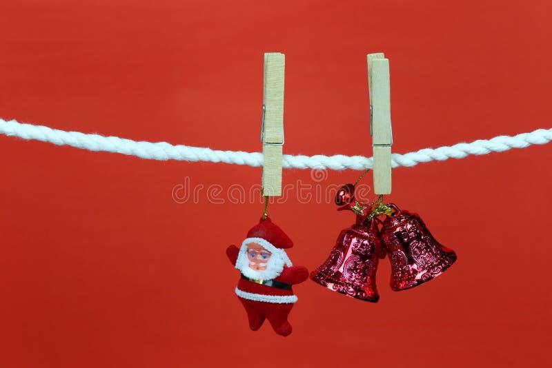 Η κούκλα Santa κρεμά στη σκοινί για άπλωμα και έχει το διάστημα αντιγράφων με το κόκκινο υπόβαθρο στοκ εικόνα