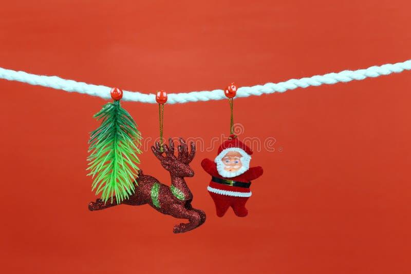 Η κούκλα Santa κρεμά στη σκοινί για άπλωμα και έχει το διάστημα αντιγράφων με το κόκκινο υπόβαθρο στοκ φωτογραφία με δικαίωμα ελεύθερης χρήσης