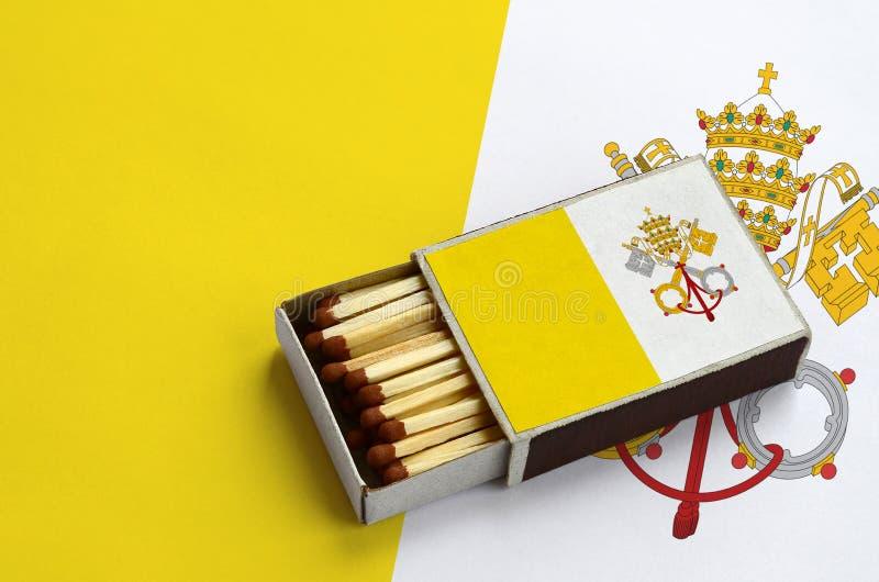 Η κρατική σημαία πόλεων του Βατικανού παρουσιάζεται σε ένα ανοικτό σπιρτόκουτο, το οποίο γεμίζουν με τις αντιστοιχίες και βρίσκετ στοκ εικόνες