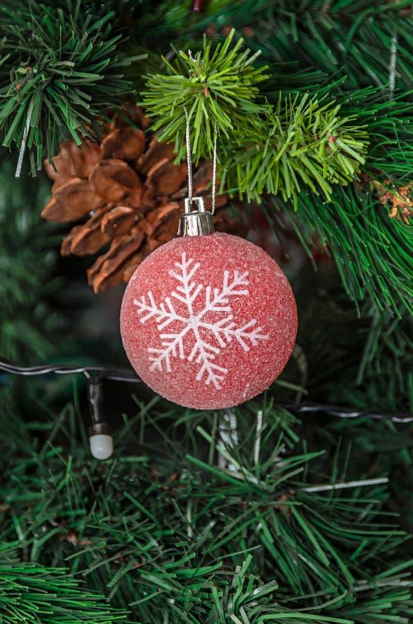 Η κρεμώντας διακόσμηση χριστουγεννιάτικων δέντρων, κόκκινη σφαίρα με snowflake, κλείνει στοκ εικόνες