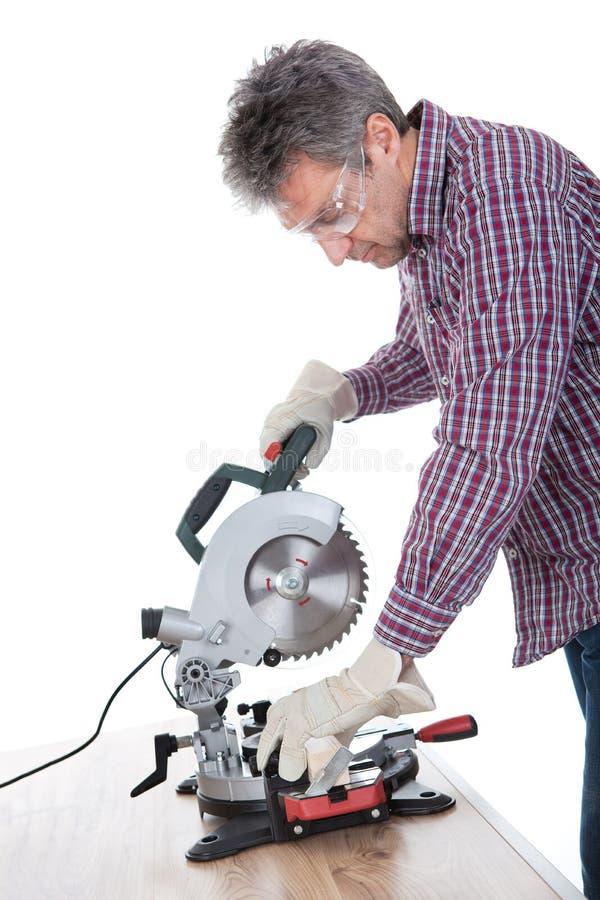 η κυκλική κοπή είδε την ξυλεία χρησιμοποιώντας τον εργαζόμενο στοκ φωτογραφίες
