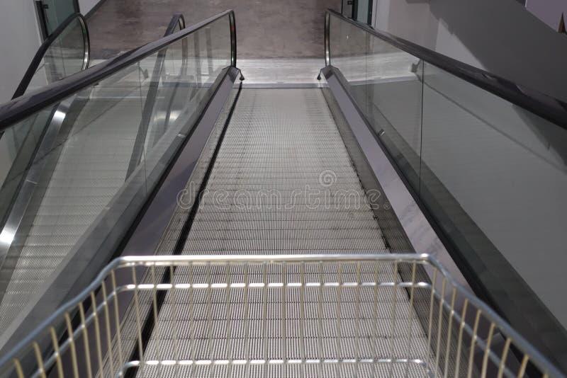 Η κυλιόμενη σκάλα για το αυτοκίνητο αγορών καροτσακιών αναχωρεί μέσα σημαμένο κατάστημα για τη χρήση πελατών σε περίπτωση που στοκ φωτογραφίες