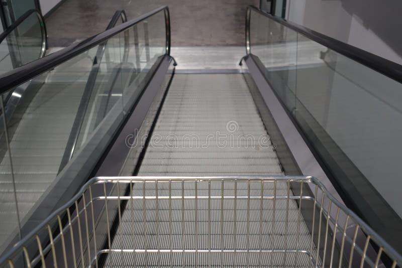 Η κυλιόμενη σκάλα για το αυτοκίνητο αγορών καροτσακιών αναχωρεί μέσα σημαμένο κατάστημα για τη χρήση πελατών σε περίπτωση που στοκ εικόνα με δικαίωμα ελεύθερης χρήσης