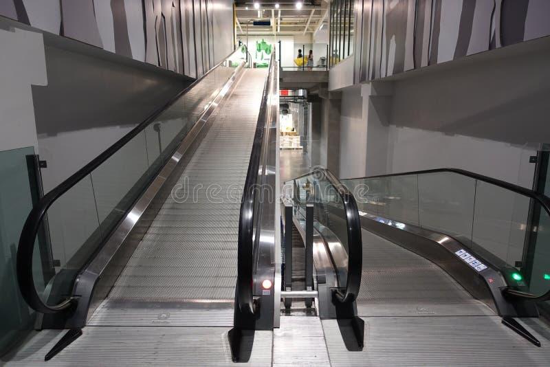 Η κυλιόμενη σκάλα για το αυτοκίνητο αγορών καροτσακιών αναχωρεί μέσα σημαμένο κατάστημα για τη χρήση πελατών σε περίπτωση που στοκ εικόνες με δικαίωμα ελεύθερης χρήσης