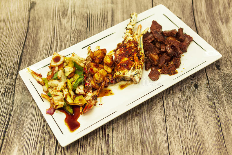 Η κυματωγή και η τύρφη, ο τηγανισμένος αστακός και ο juicy πάσσαλος με διακοσμούν από τα τηγανισμένα λαχανικά στοκ φωτογραφίες