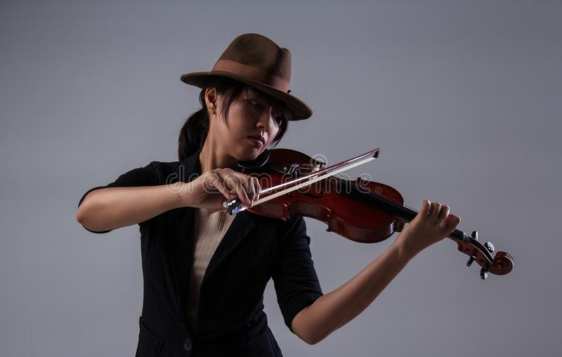 Η κυρία με το καφετί καπέλο παίζει το βιολί, έβαλε το βιολί στο αριστερό βιολί τόξων ώμων και λαβής με δεξή στοκ φωτογραφία με δικαίωμα ελεύθερης χρήσης