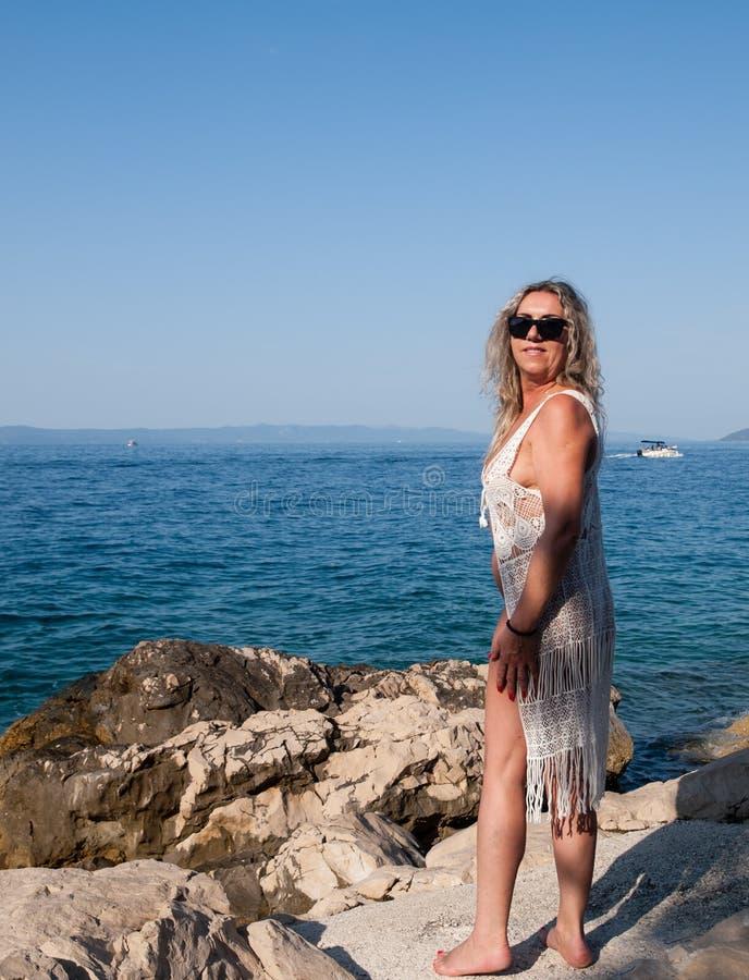 Η κυρία ποζάρει στην παραλία στοκ εικόνα