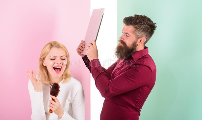 Η κυρία τραγουδά τη χρησιμοποίηση της βούρτσας τρίχας ως μικρόφωνο ενώ το άτομο που ενοχλήθηκε το lap-top της μετάβαση κτύπησε Κα στοκ εικόνα με δικαίωμα ελεύθερης χρήσης