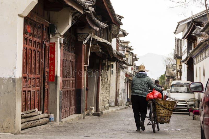 Η κυρία ωθεί το ποδήλατο μέσω της πόλης του Δαλιού σε Yunnan στοκ φωτογραφίες