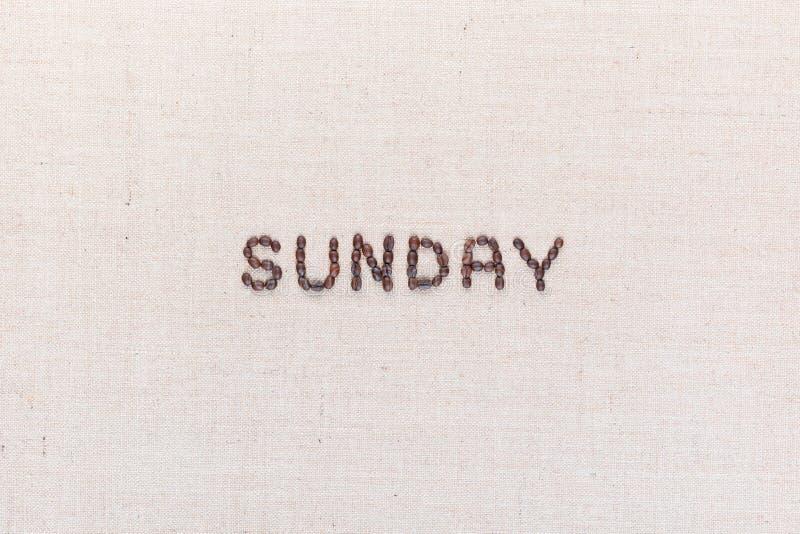 Η Κυριακή λέξης που γράφεται με τα φασόλια καφέ, που ευθυγραμμίζονται στο κέντρο στοκ φωτογραφίες