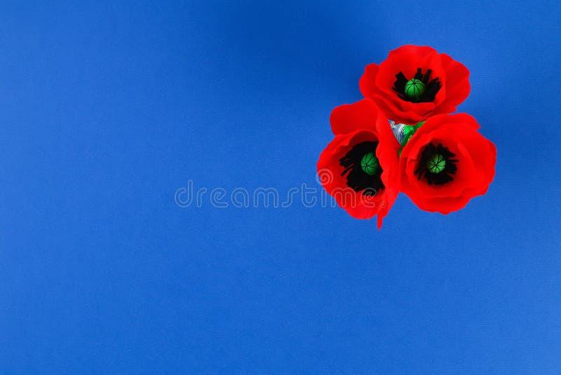 Η κόκκινη ημέρα Anzac παπαρουνών εγγράφου Diy, ενθύμηση, θυμάται, η ημέρα μνήμης crepe το έγγραφο για το μπλε υπόβαθρο στοκ φωτογραφία
