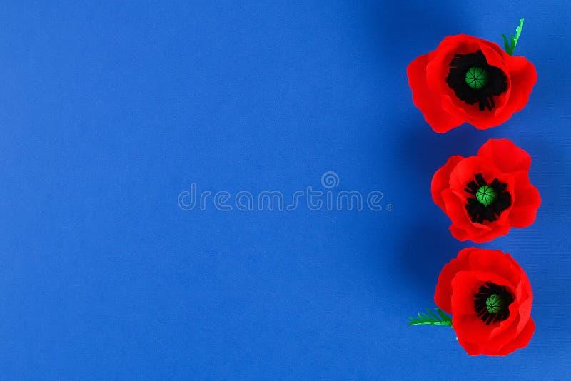 Η κόκκινη ημέρα Anzac παπαρουνών εγγράφου Diy, ενθύμηση, θυμάται, η ημέρα μνήμης crepe το έγγραφο για το μπλε υπόβαθρο στοκ φωτογραφίες με δικαίωμα ελεύθερης χρήσης