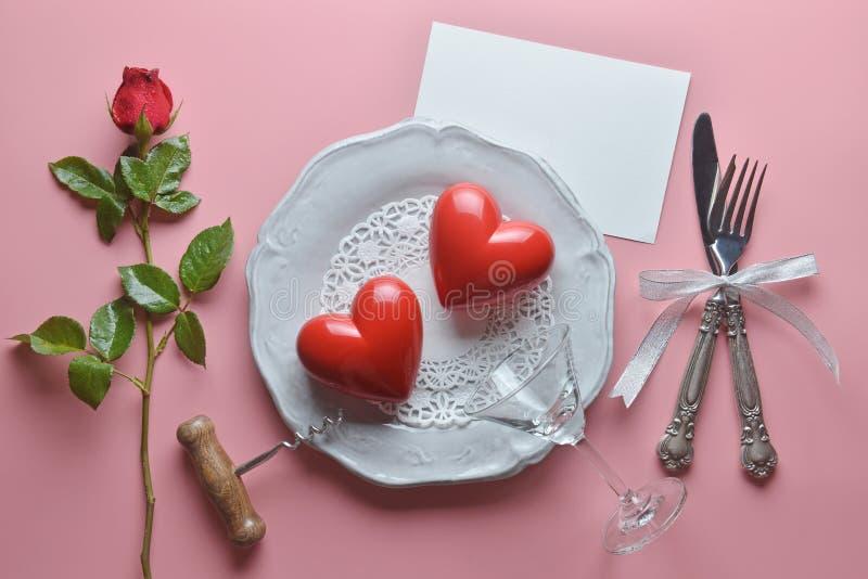 Η κόκκινη καρδιά ζευγών, ανοιχτήρι κρασιού, γυαλί κοκτέιλ στο άσπρο πιάτο, με το δίκρανο και το μαχαίρι στην κορδέλλα, αυξήθηκε,  στοκ εικόνες με δικαίωμα ελεύθερης χρήσης