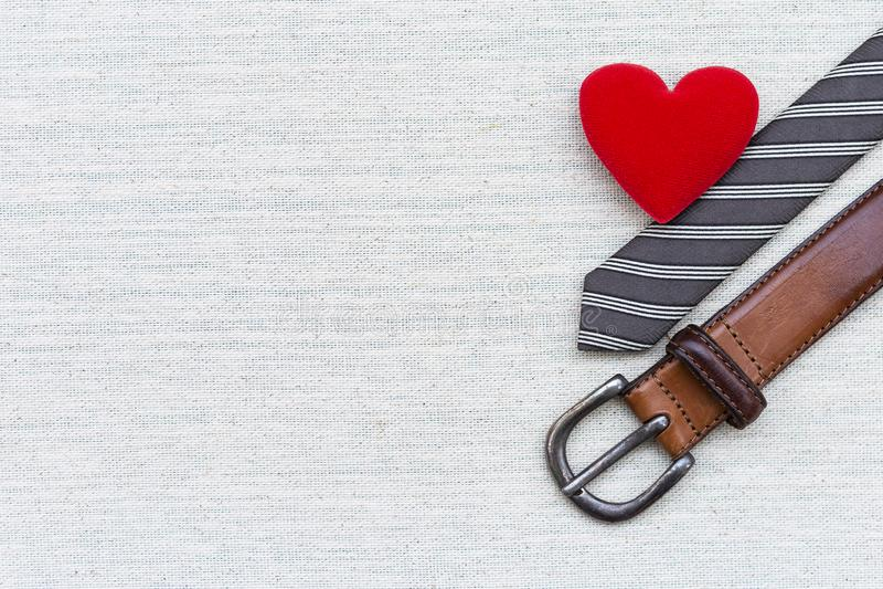 Η κόκκινη καρδιά με τα άτομα διαμορφώνει τη ζώνη δέρματος και τη γραπτή γραβάτα με το διάστημα στο υπόβαθρο σύστασης καμβά στοκ εικόνες