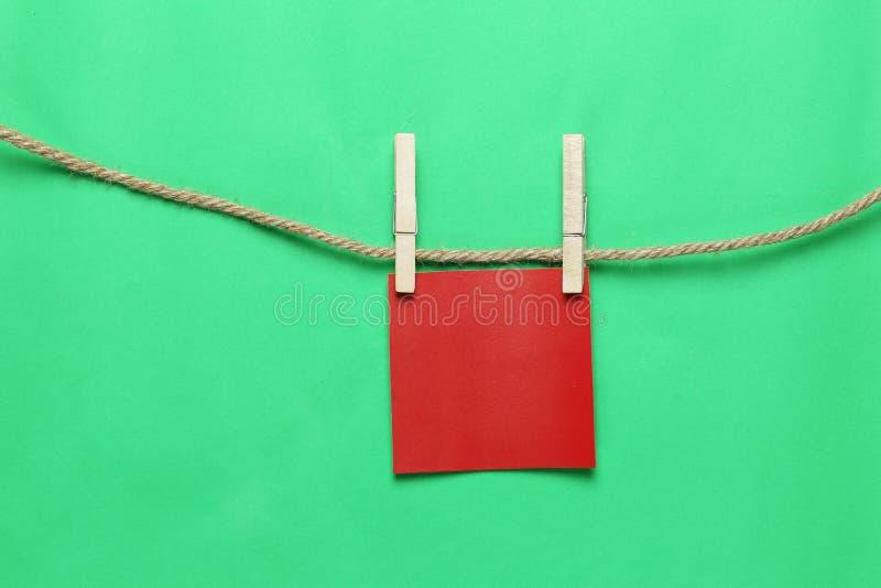 Η κόκκινη σημείωση εγγράφου κρεμά στο σχοινί κάνναβης και έχει το διάστημα αντιγράφων στοκ εικόνες