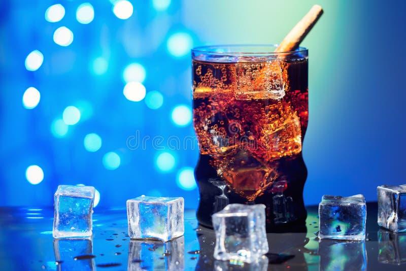 Η κόλα στην κατανάλωση του γυαλιού με το γλυκό σπινθήρισμα κύβων πάγου που ενώνεται με διοξείδιο του άνθρακα πίνει το γρήγορο φαγ στοκ εικόνα