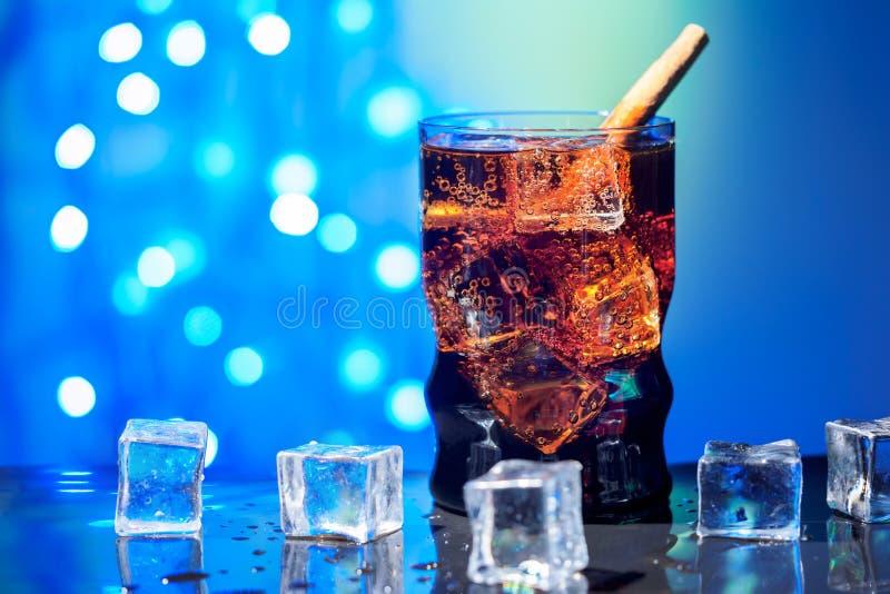 Η κόλα στην κατανάλωση του γυαλιού με το γλυκό σπινθήρισμα κύβων πάγου που ενώνεται με διοξείδιο του άνθρακα πίνει το γρήγορο φαγ στοκ εικόνα με δικαίωμα ελεύθερης χρήσης