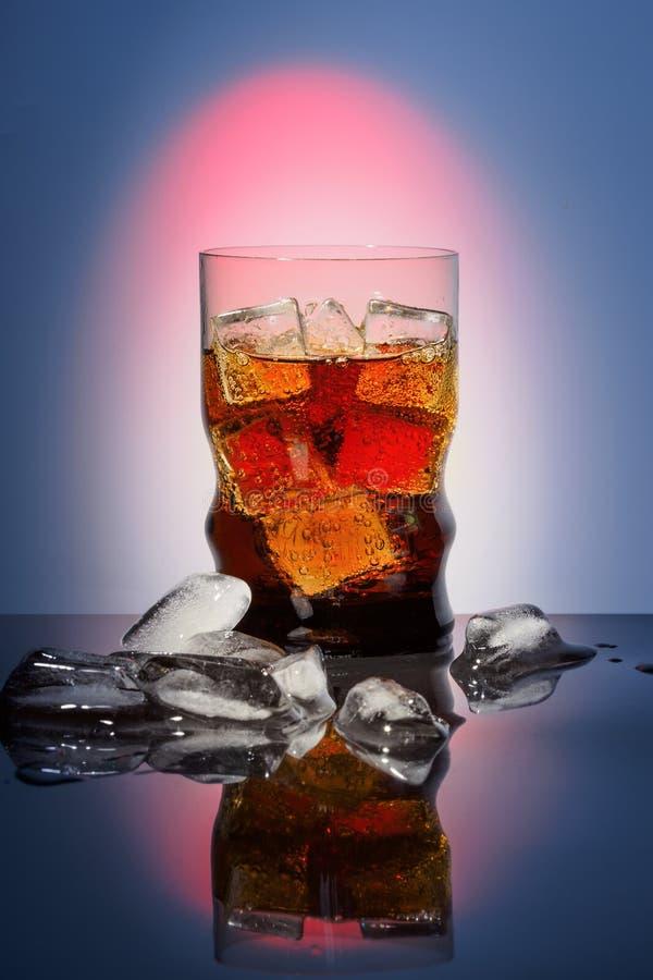 Η κόλα στην κατανάλωση του γυαλιού με το γλυκό σπινθήρισμα πάγου που ενώνεται με διοξείδιο του άνθρακα πίνει το γρήγορο φαγητό πο στοκ εικόνες