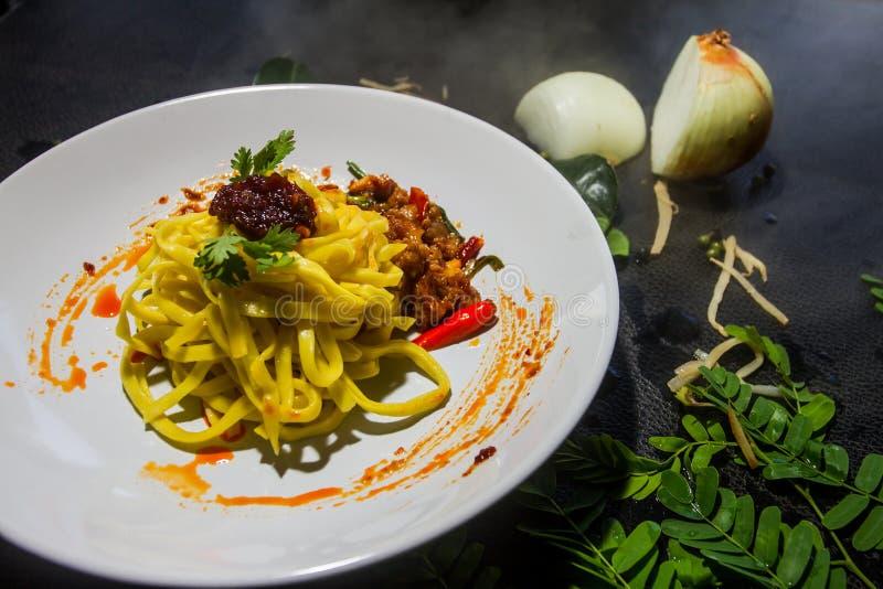 Η κόλλα τσίλι τηγάνισε τα κίτρινα νουντλς προετοιμάζεται και χρησιμεύεται ως το υπόβαθρο ταϊλανδικός παραδοσιακός τροφίμων στοκ φωτογραφία με δικαίωμα ελεύθερης χρήσης