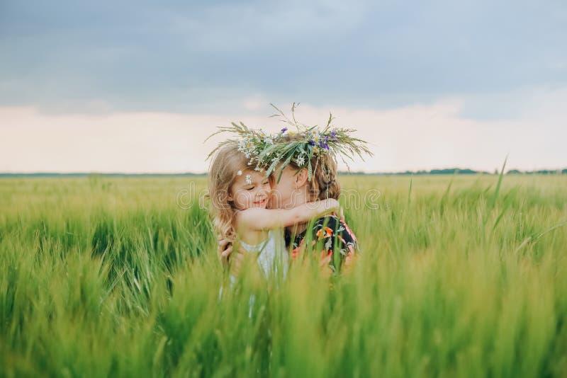 Η κόρη δίνει τη φύση αγκαλιασμάτων λουλουδιών στεφανιών μητέρων στοκ εικόνες