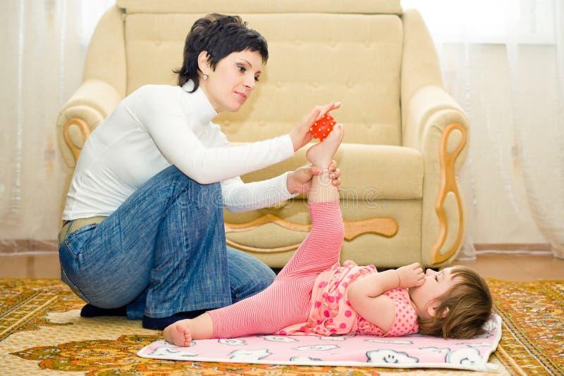 η κόρη κάνει τη μητέρα μασάζ στοκ εικόνες