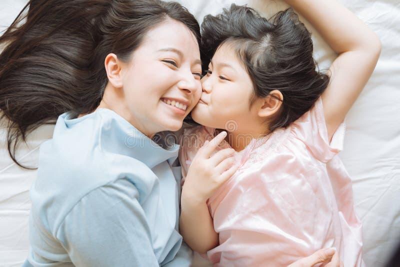 Η κόρη φιλά το μάγουλο της μητέρας της και αγκαλιάζοντας στην κρεβατοκάμαρα Ευτυχής ασιατική οικογένεια στοκ φωτογραφίες