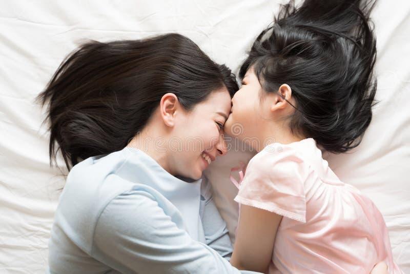 Η κόρη φιλά το μέτωπο της μητέρας της και αγκαλιάζοντας στην κρεβατοκάμαρα Ευτυχής ασιατική οικογένεια στοκ φωτογραφία με δικαίωμα ελεύθερης χρήσης