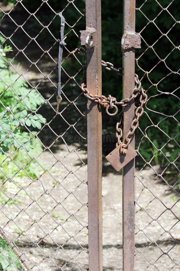 η κλειδαριά μετάλλων κλείνει την πύλη με μια αλυσίδα και το κλειδί κρεμά πλησίον στοκ φωτογραφία