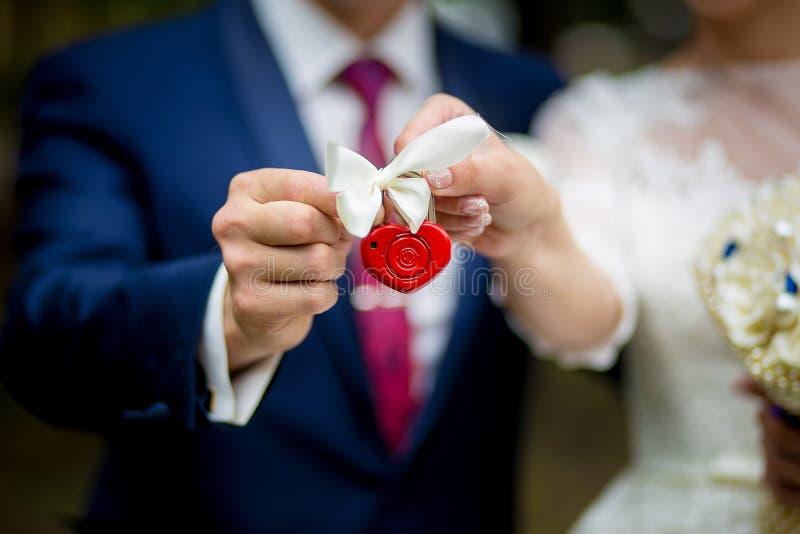 Η κλειδαριά στα χέρια του πρόσφατα παντρεμένου ζευγαριού, κινηματογράφηση σε πρώτο πλάνο στοκ εικόνα με δικαίωμα ελεύθερης χρήσης
