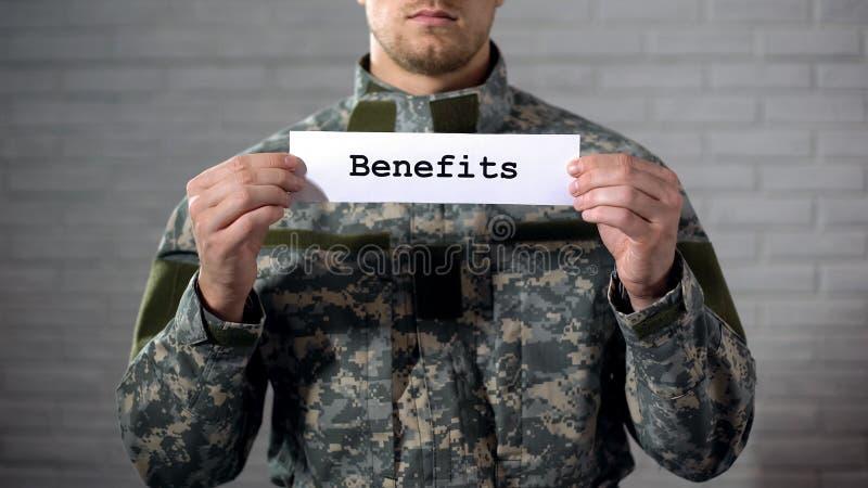 Η λέξη οφελών που γράφεται στο σημάδι στα χέρια του αρσενικού στρατιώτη, παλαίμαχοι υποστηρίζει, ενίσχυση στοκ εικόνες με δικαίωμα ελεύθερης χρήσης