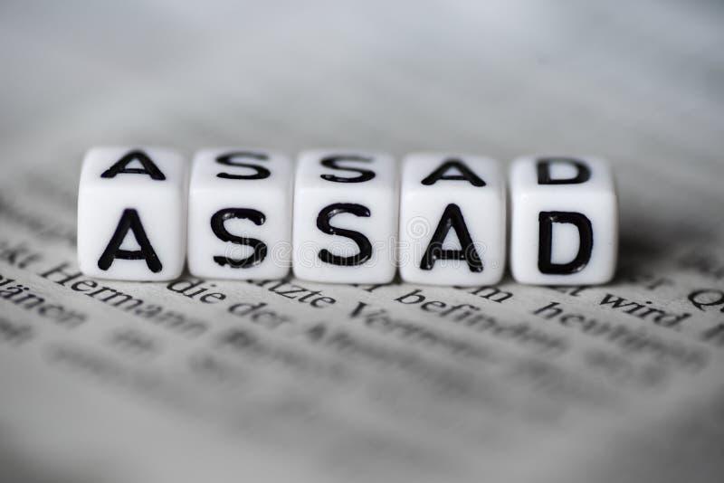 Η λέξη ASSAD διαμόρφωσε από τους ξύλινους φραγμούς αλφάβητου στην εφημερίδα στοκ εικόνα