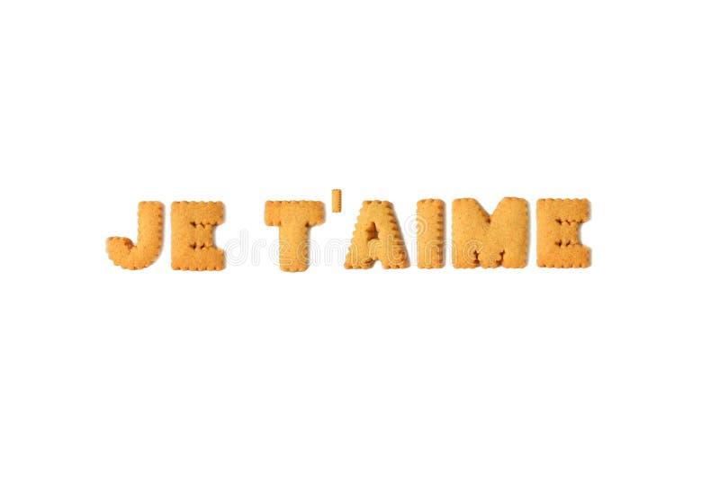 """Η λέξη JE Τ """"AIME ή Σ' ΑΓΑΠΏ στα γαλλικά που συλλάβισαν με το αλφάβητο διαμόρφωσε τα μπισκότα στο άσπρο υπόβαθρο στοκ φωτογραφία"""