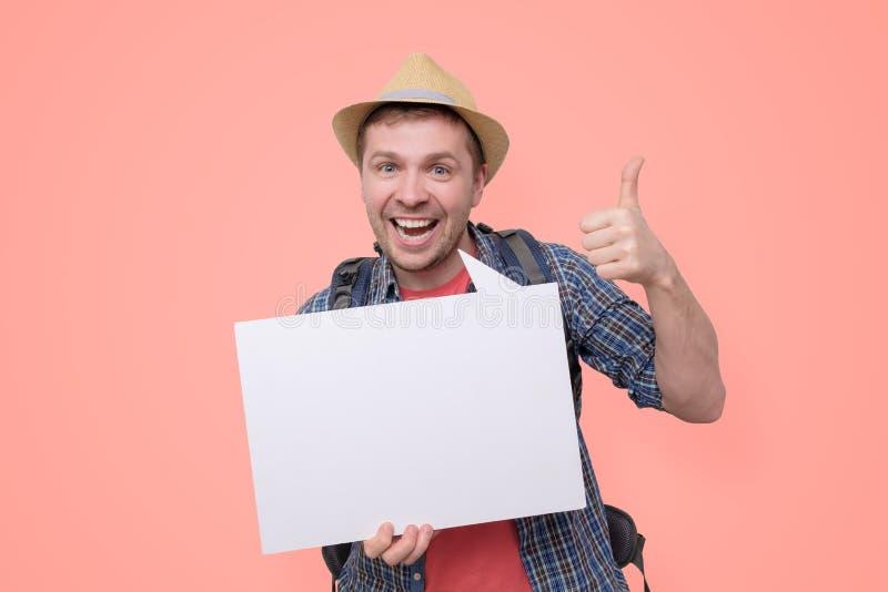 Η λαβή τουριστών και παρουσιάζει κενό πίνακα με τον αντίχειρα επάνω στοκ φωτογραφίες