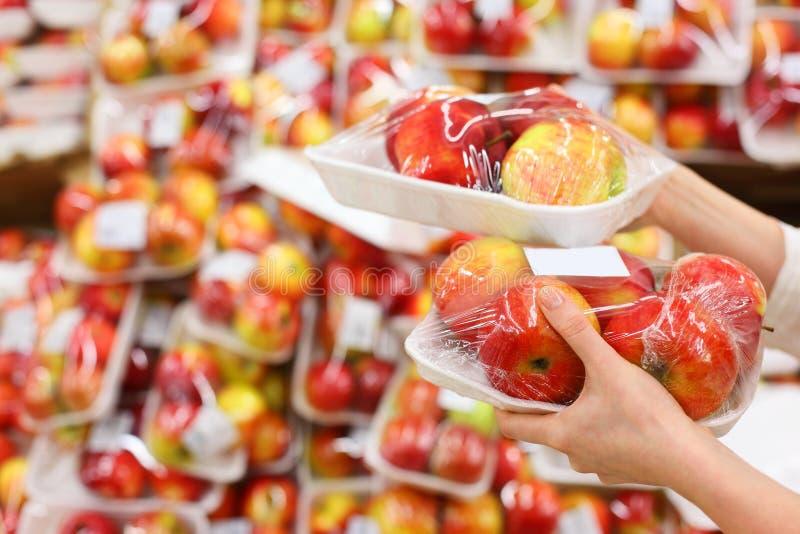η λαβή χεριών κοριτσιών μήλων συσκεύασε το κατάστημα στοκ εικόνες