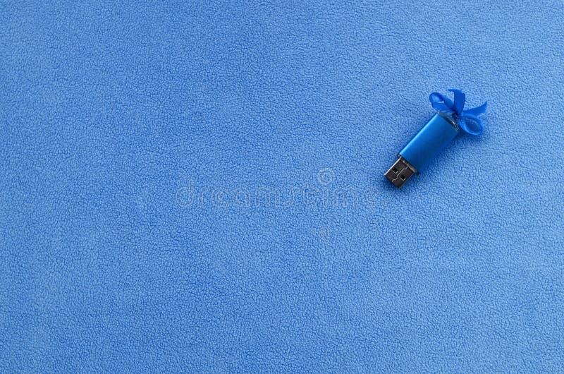 Η λαμπρή μπλε κάρτα αστραπιαίας σκέψης usb με ένα μπλε τόξο βρίσκεται σε ένα κάλυμμα του μαλακού και γούνινου ανοικτό μπλε υφάσμα στοκ εικόνα