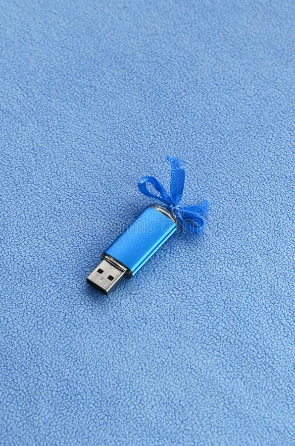 Η λαμπρή μπλε κάρτα αστραπιαίας σκέψης usb με ένα μπλε τόξο βρίσκεται σε ένα κάλυμμα του μαλακού και γούνινου ανοικτό μπλε υφάσμα στοκ εικόνες με δικαίωμα ελεύθερης χρήσης