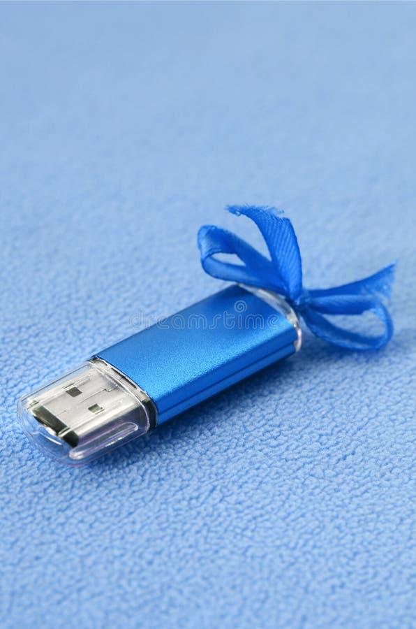 Η λαμπρή μπλε κάρτα αστραπιαίας σκέψης usb με ένα μπλε τόξο βρίσκεται σε ένα κάλυμμα του μαλακού και γούνινου ανοικτό μπλε υφάσμα στοκ φωτογραφία