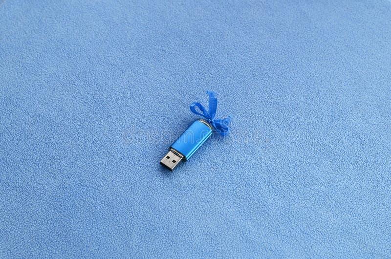 Η λαμπρή μπλε κάρτα αστραπιαίας σκέψης usb με ένα μπλε τόξο βρίσκεται σε ένα κάλυμμα του μαλακού και γούνινου ανοικτό μπλε υφάσμα στοκ φωτογραφίες με δικαίωμα ελεύθερης χρήσης