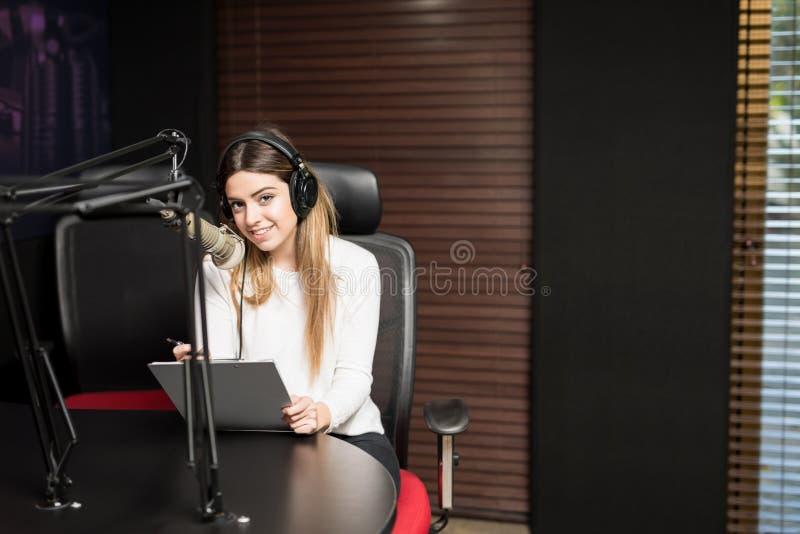 Η λατινική γυναίκα που φιλοξενεί μια συζήτηση παρουσιάζει στο ραδιοσταθμό στοκ φωτογραφίες με δικαίωμα ελεύθερης χρήσης