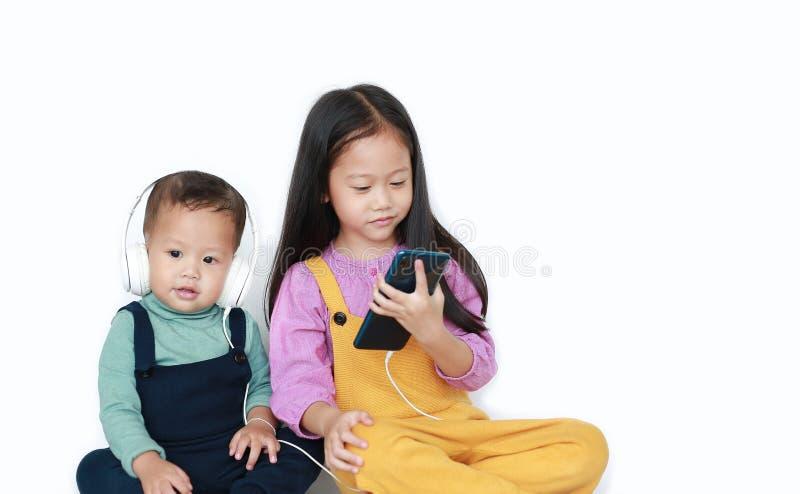 Η λατρευτή ασιατική παλαιότερη αδελφή και λίγος αδελφός που μοιράζονται απολαμβάνονται τη μουσική ακούσματος με τα ακουστικά από  στοκ φωτογραφίες